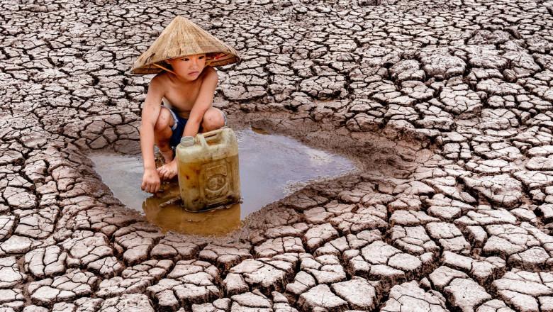 copil adunând apă