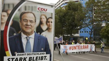 Câțiva protestatari din Berlin trec în marș pe lângă un afiș electoral al lui Armin Laschet.
