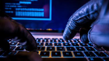 Hacker care tastează la un laptop.