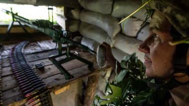 soldat ucrainean cu casca, mitraleria si munitie ascuns in adapost