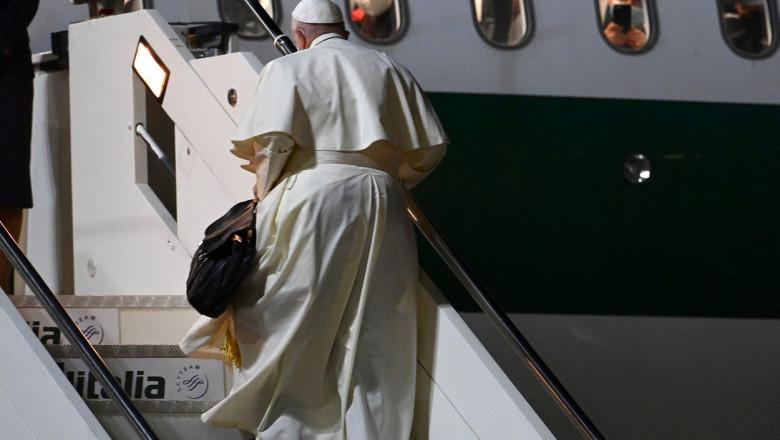 Papa Francis urcă scările pentru a se îmbarca într-un avion