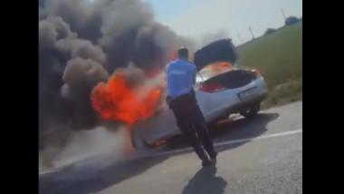 O mașină arde la marginea șoselei.