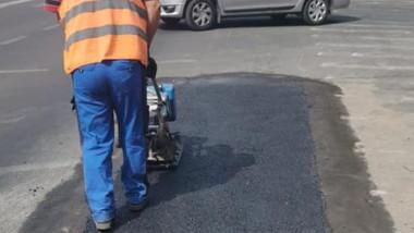 Un bărbat tasează o plombă de asflat pe stradă.