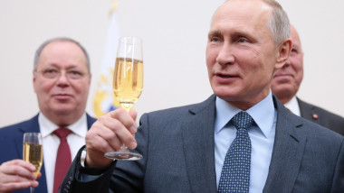 Vladimir Putin zâmbește cu un pahar de șampanie în mână