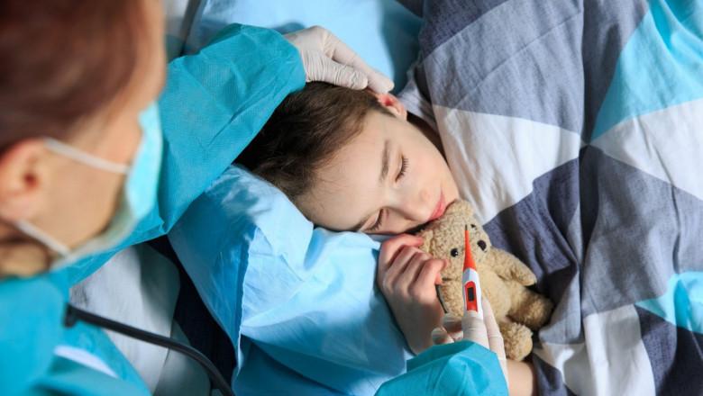 copil care doarme cu ursuletul si caruia i se ia temperatura