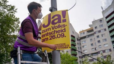 un tanar fixeaza pe un stalp un afis favorabil campaniei pentru exproprierea marilor proprietari de locuinte din berlin
