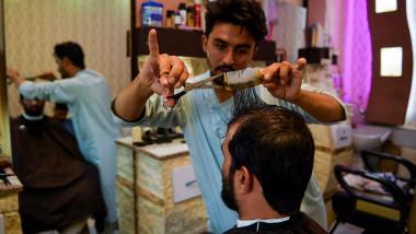 Un frizer tunde un client în orașul Herat din Afganistan.