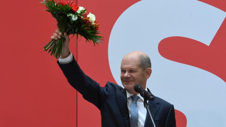 Ministrul german de finanțe, vicecancelarul și candidatul partidului social-democrat pentru funcția de cancelar al Germanei, Olaf Scholz, salută membrii social-democrați adunați luni dimineață la sediul din Berlin al SPD, în timp ce ține un buchet de flori în mână