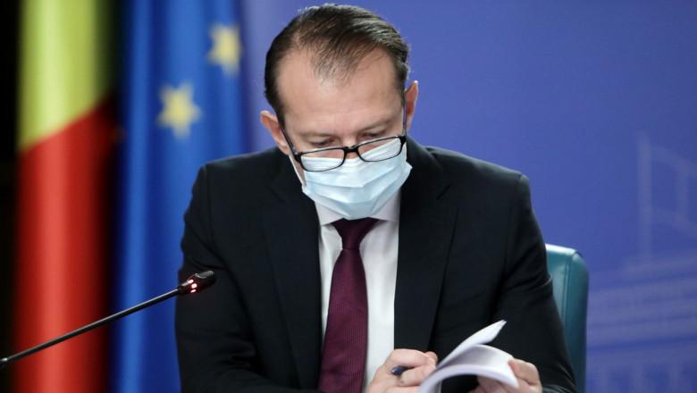Florin Cîțu se uită pe niște documente într-o ședință de guvern.