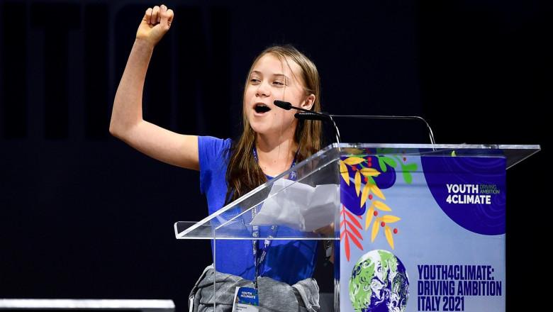 Greta Thunberg cu mâna ridicată la pupitru