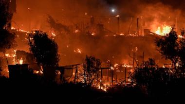 zonă cu clădiri în flăcări cu atmosferă portocalie și fum