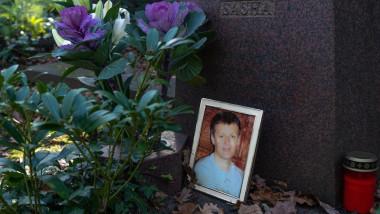 Flori și o fotografie înrămată pe un mormânt