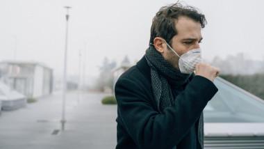 barbat cu masca la gură tuseste din cauza poluării