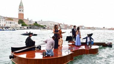 Un cvartet interpretează Vivaldi pe o barcă gigantică în formă de vioară, pe canalele Veneției.