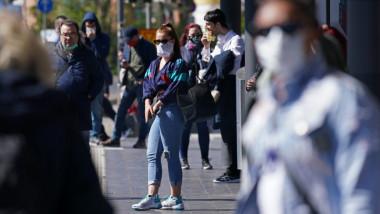 oameni cu masti pe strada
