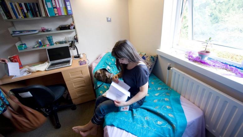 studenta in camera de camin citeste pe pat