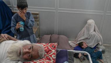 Oameni așteaptă să fie tratați pe holurile unui spital din Kandahar