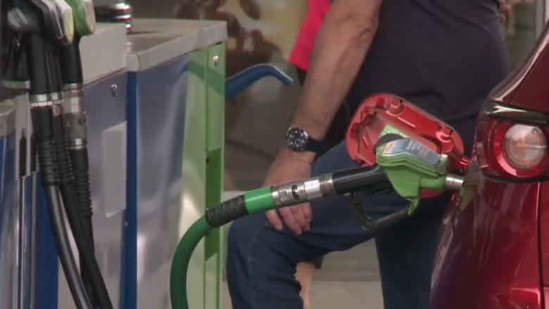 Un bărbat alimentează mașina cu carburant.