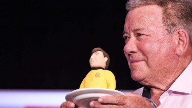 Actor William Shatner, best known for his portrayal of Captain James T. Kirk of the USS Enterprise in the Star Trek television series and movies, holds a portion of a birthday cake presented to him at a Q&amp