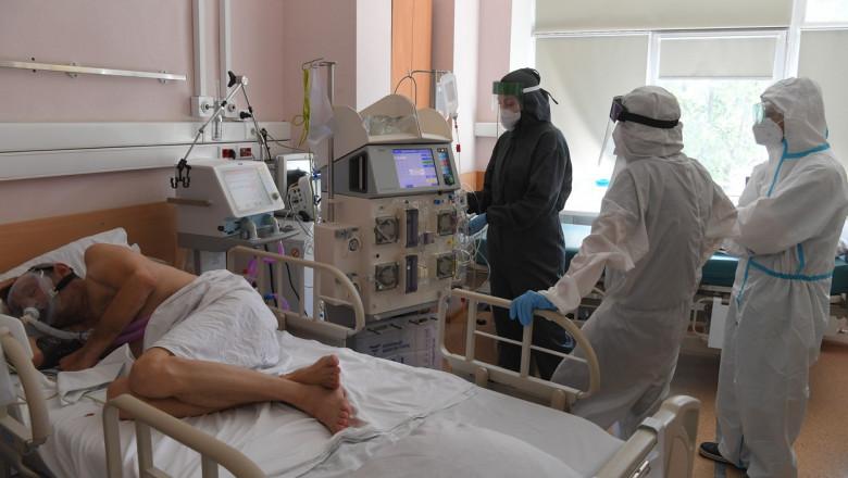 pacient de coronavirus cu mască pe pat și medici care îl îngrijesc