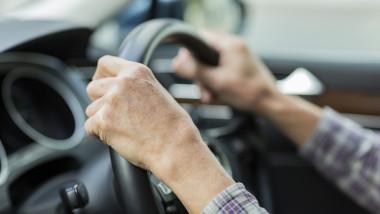 barbat cu mainile pe volan