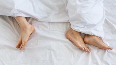 Problems in family relationship. Feet of man and woman in white bed at distance