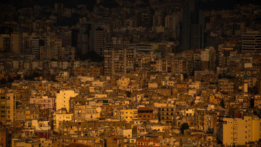 The setting sun lights buildings experiencing electrical outages in the suburbs of Beirut