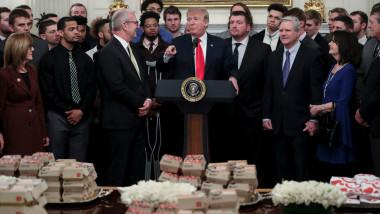 donald trump in mijlocul unui grup de oameni cu fast food si hamburgeri pe masa in fata