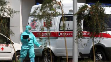 Un cadru medical în combinezon, lângă o ambulanță, în Rusia.