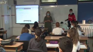Elevi și profesoară în sala de clasă.