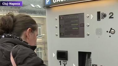 O femeie plătește parcarea la automat.