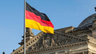 Drapelul Germaniei în fața unei clădiri.