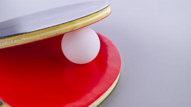 O minge de tenis de masă între două palete.