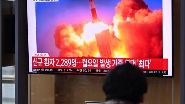 Un bărbat privește spre un televizor în care apare lansarea unei rachete balistice