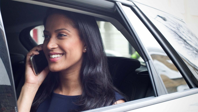 Business woman sitting in car, using smartphone