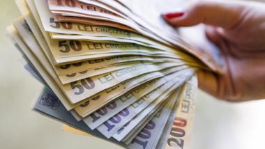 bancnote de 50, 100 si 200 de lei tinute rasfirate intre degetele unei doamne