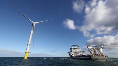 turbina eoliana pe mare langa o nava