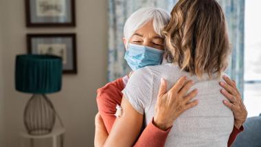 o femee in varsta cu masca imbratiseaza o femeie tanara cu plasture de vaccin pe brat