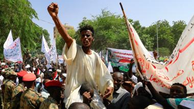 Bărbat cu pumnul ridicat într-o mare de oameni la un protest