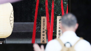 Un bărbat cu spatele se roagă la un sanctuar șinto din Japonia