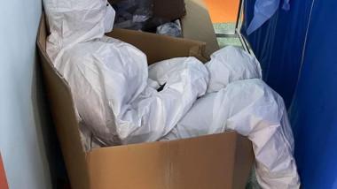O asistentă îmbrăcată în combinezon se odihnește într-o cutie de carton.
