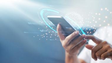 utilizator care tine in mana un smartphone in jurul caruia o grafica sugereaza transferul de date