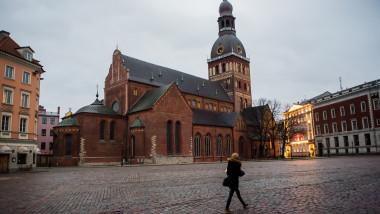 femeie singura in fata catedralei riga din letonia