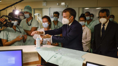 Emmanuel Macron (C) uses hand sanitiser before signing a nurse's vest as he meets with frontline staff working at the French Polynesia Hospital Centre in Papeete