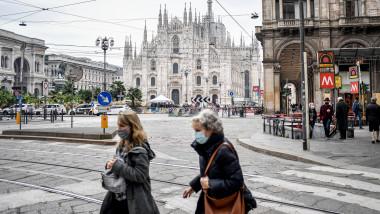 oameni cu masti in piata Duomo din Milano