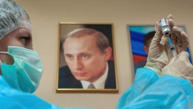 O asistentă pregătește o doză de vaccin pentru vaccinare, pe perete aflându-se un portret al lui Vladimir Putin