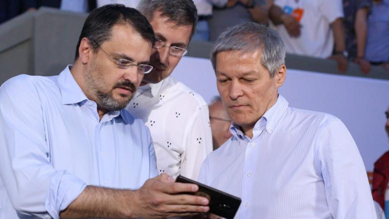 Ghinea, Barna și Cioloș se uită pe un telefon mobil.