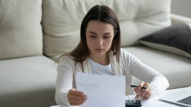 tanara care se uita pe o factura de utilitati si calculeaza cu calculator in fata
