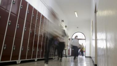 elevi alergand, in miscare, pe holul unei scoli