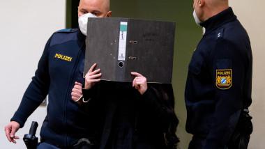 femeie își acoperă fața cu un dosar, flancată de polițiști
